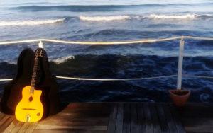 chitarra sul pontile con sfondo mare