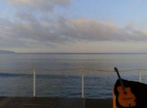 chitarra su pontile con sfondo mare e nuvole